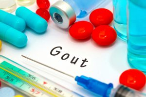 Gout - diagnosis written on a white piece of paper. Syringe and vaccine with drugs.